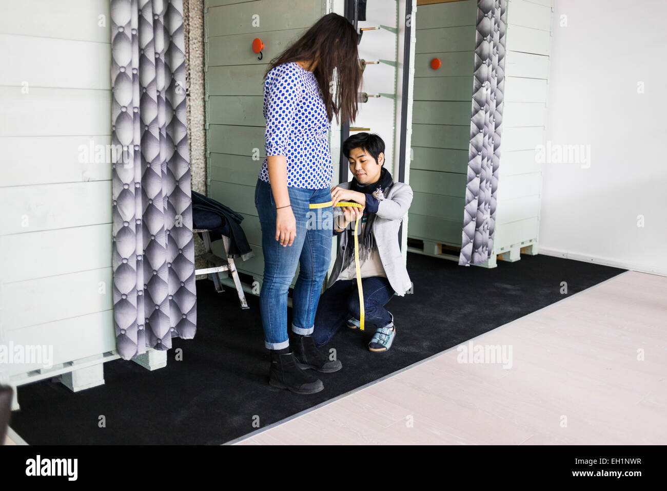 Fashion designer measuring woman's thigh in jeans factory Stock Photo
