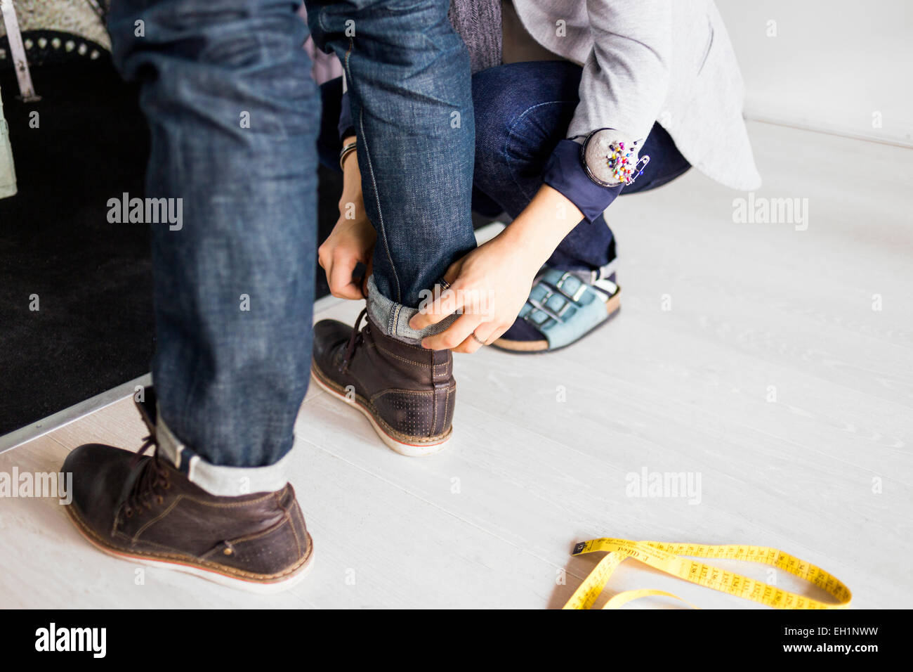 Low section of fashion designer measuring client's jeans in factory - Stock Image