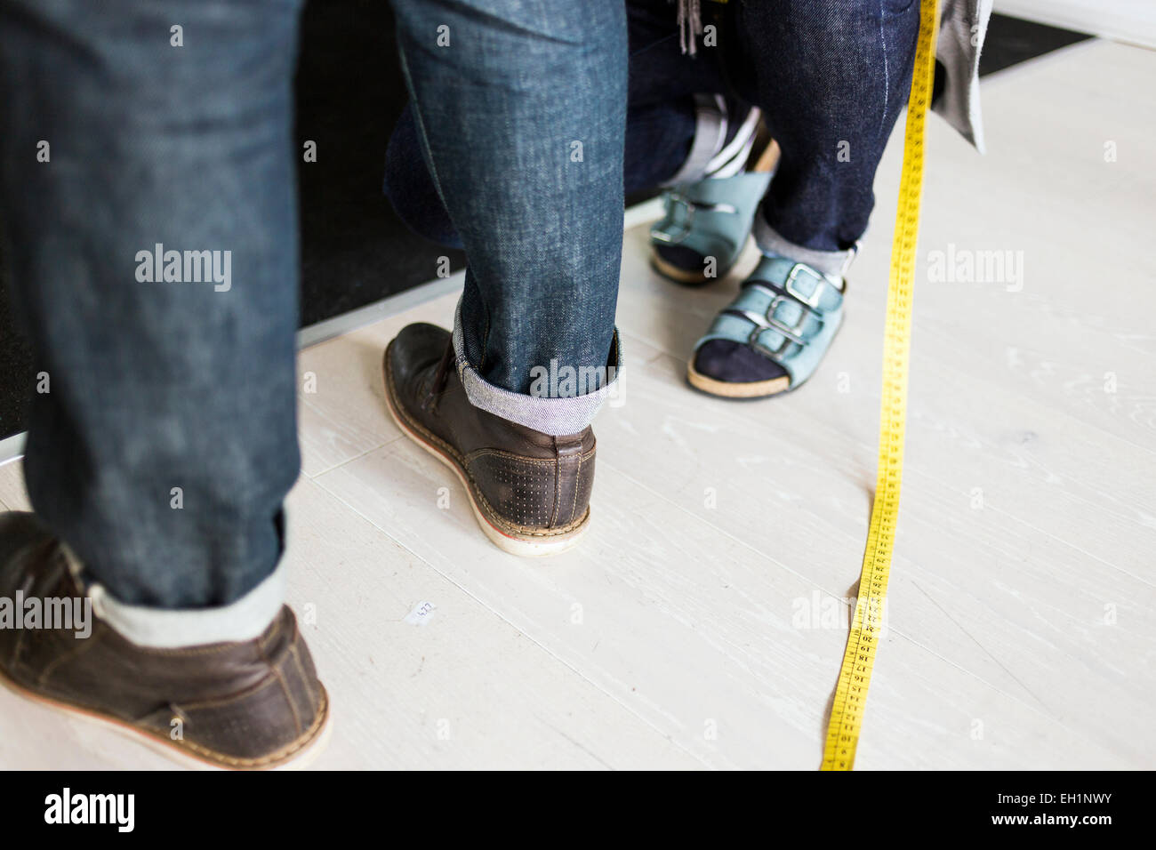 Low section of fashion designer measuring client's jeans with tape in foreground at factory - Stock Image