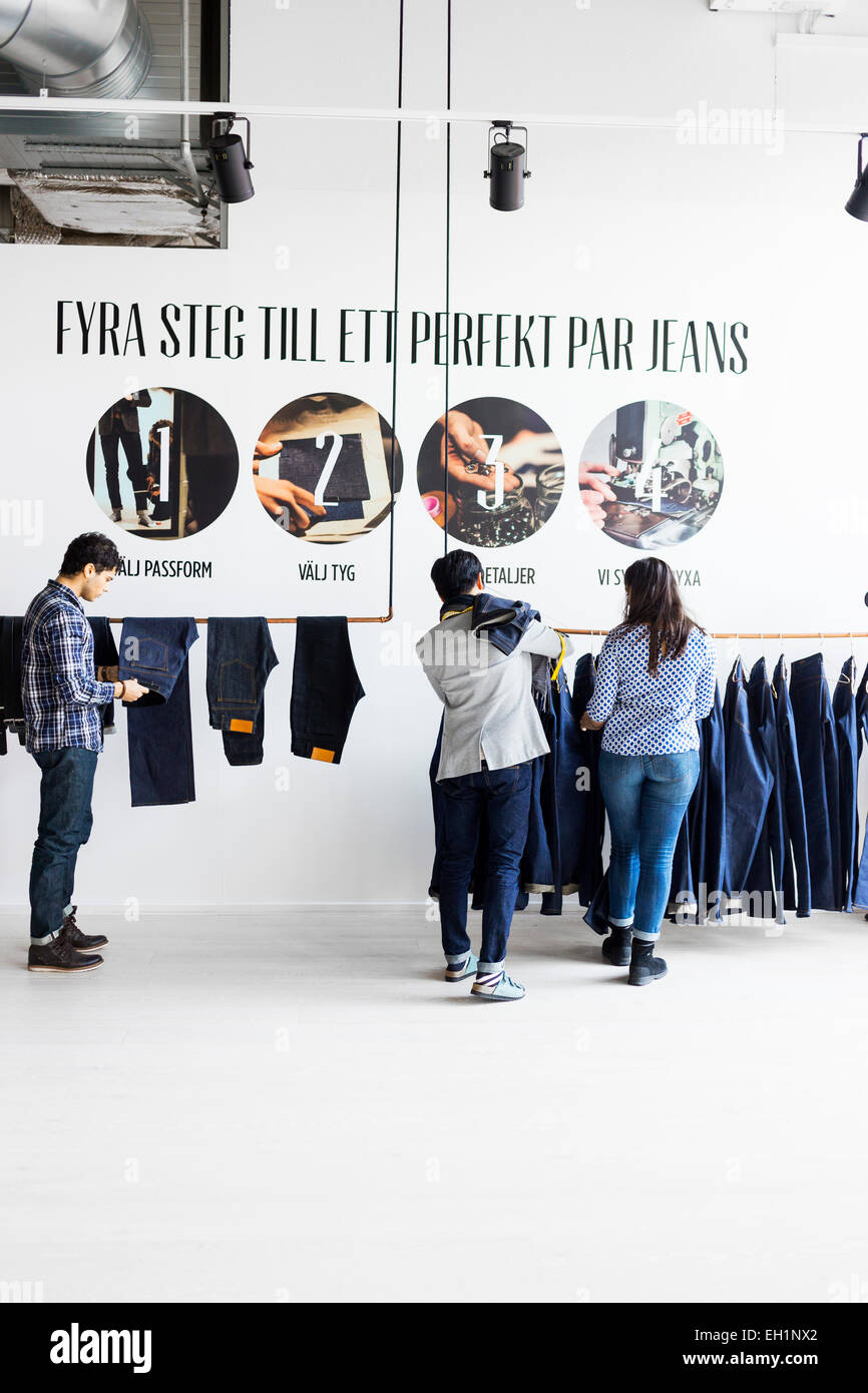 Fashion designer and clients choosing jeans in factory - Stock Image