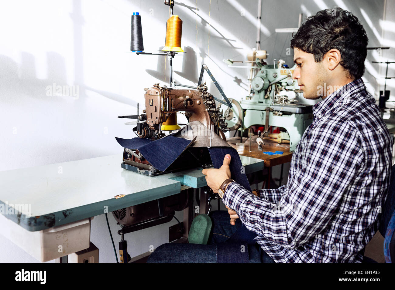 Tailor sewing jeans in factory - Stock Image