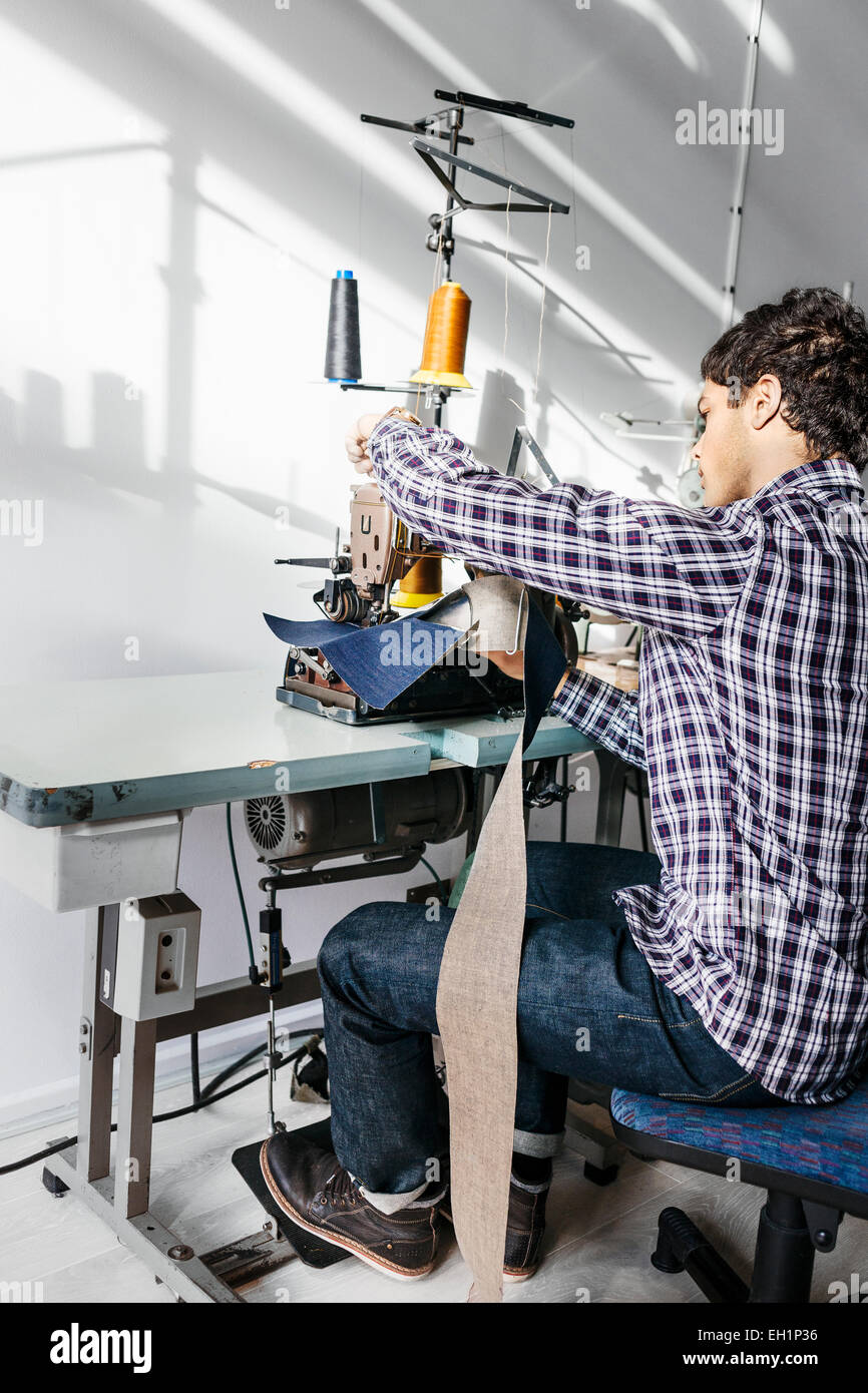 Full length of tailor sewing jeans in factory - Stock Image
