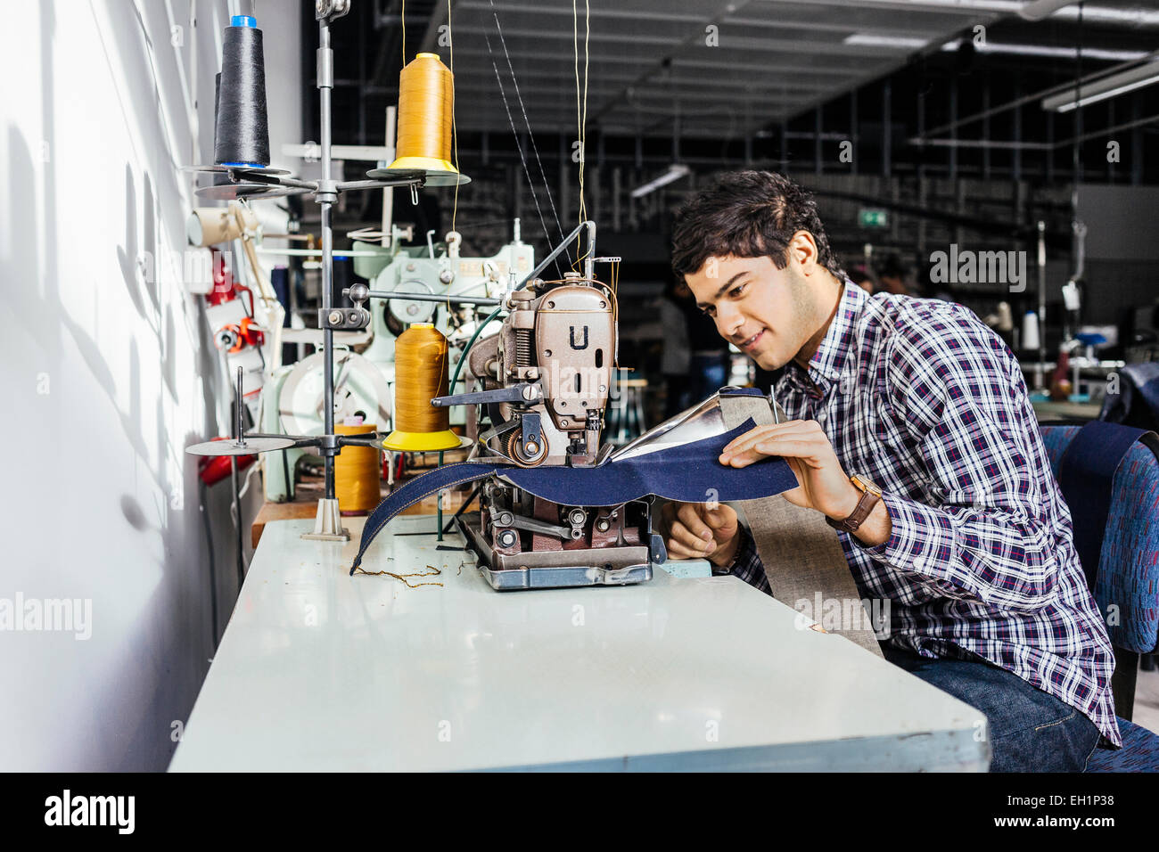 Side view of tailor sewing jeans in factory - Stock Image