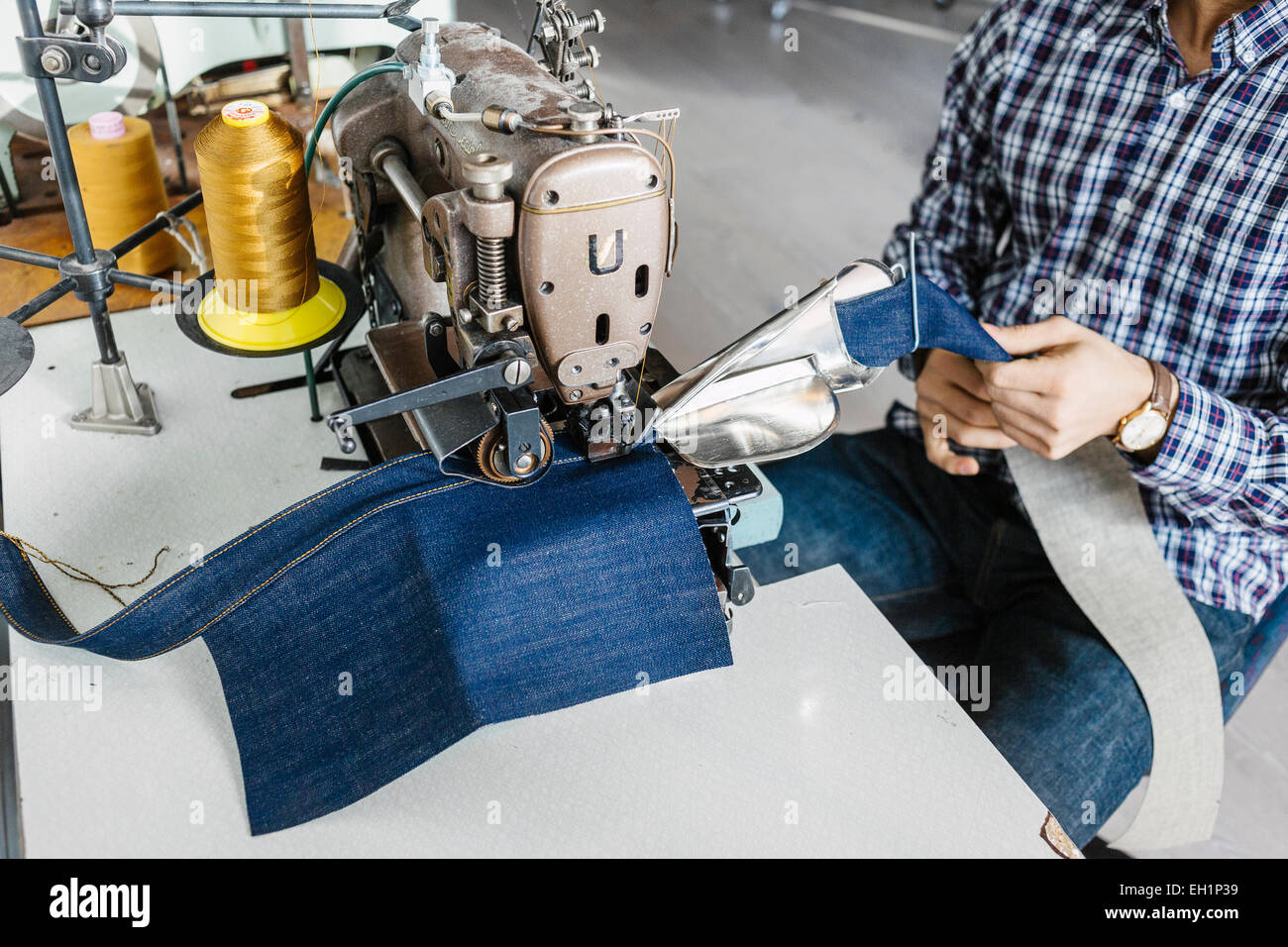 Midsection of tailor sewing jeans in factory - Stock Image