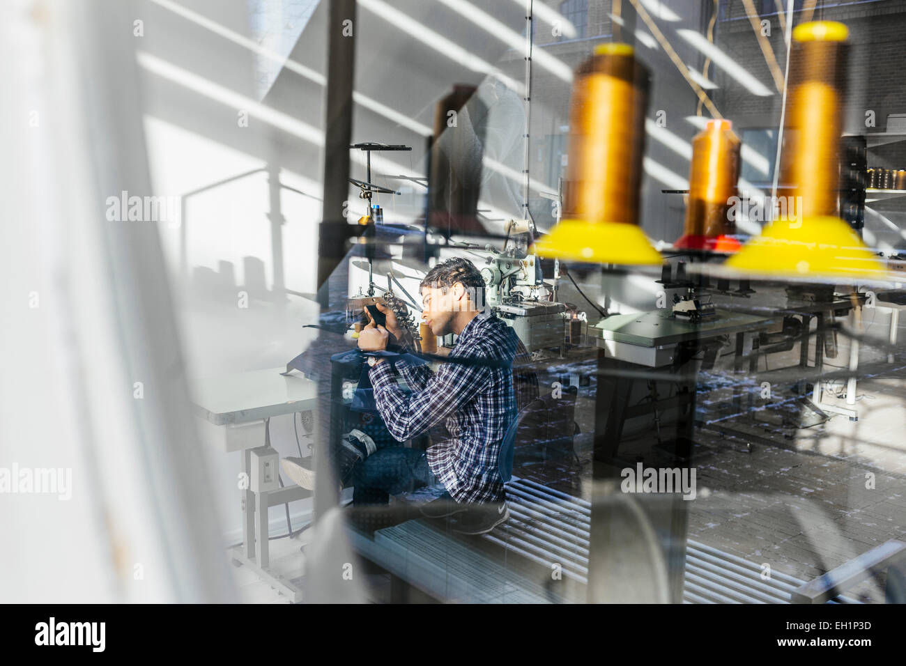 Young male tailor sewing jeans in factory - Stock Image