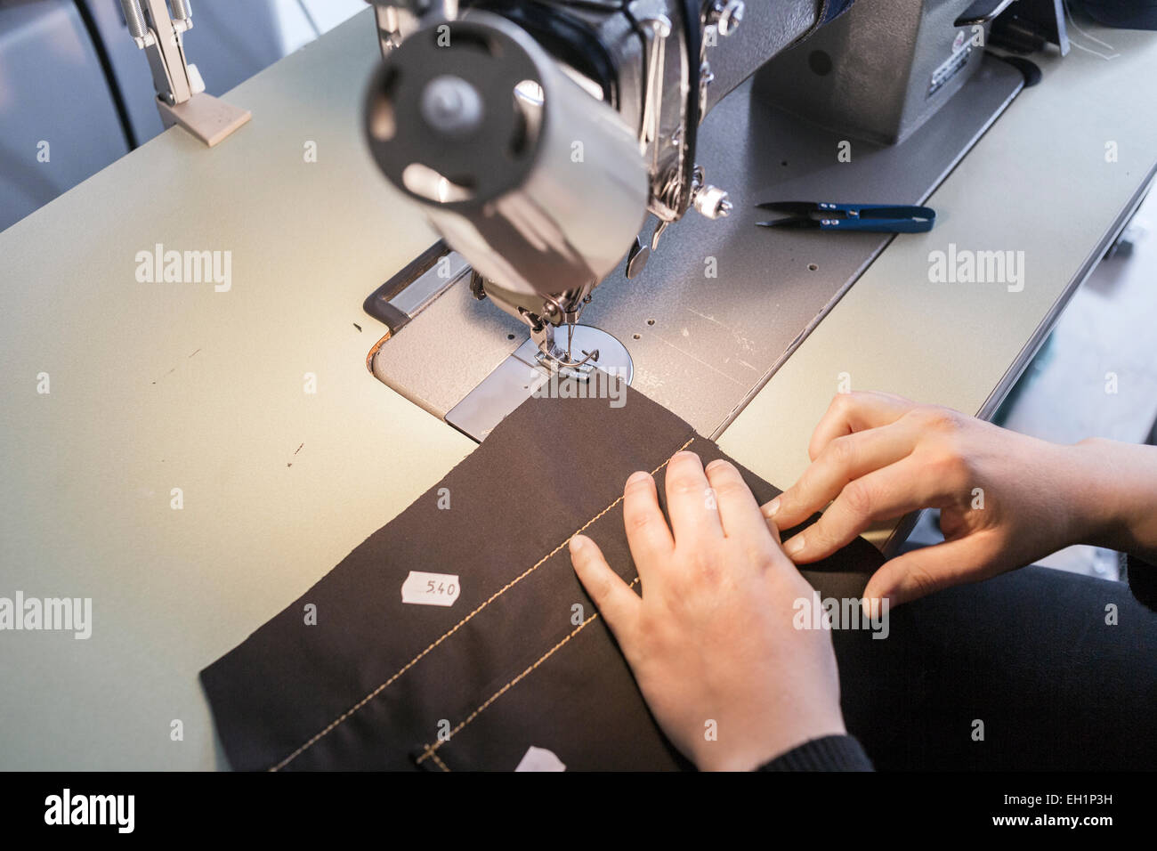 Female fashion designer using sewing machine in jeans factory - Stock Image