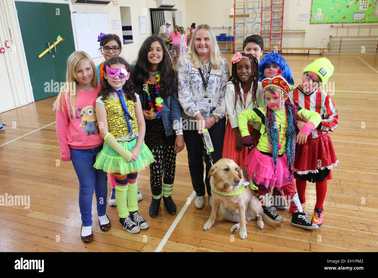 Visually impaired woman with guide dog with pupils at a primary school. - Stock Image
