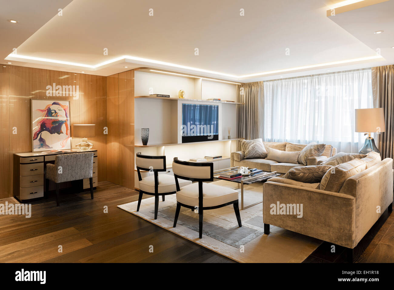 Luxurious apartment in Belgravia London. Sitting room with recessed ceiling detail lights. Study area and built - Stock Image
