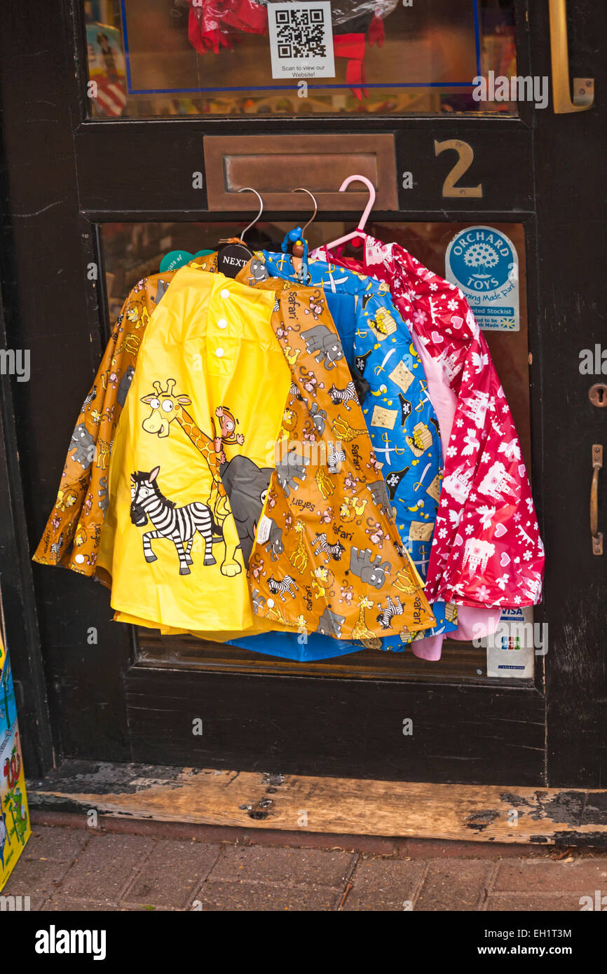 Toddlers colourful ponchos hanging from shop door at Hythe, Hampshire, UK - Stock Image