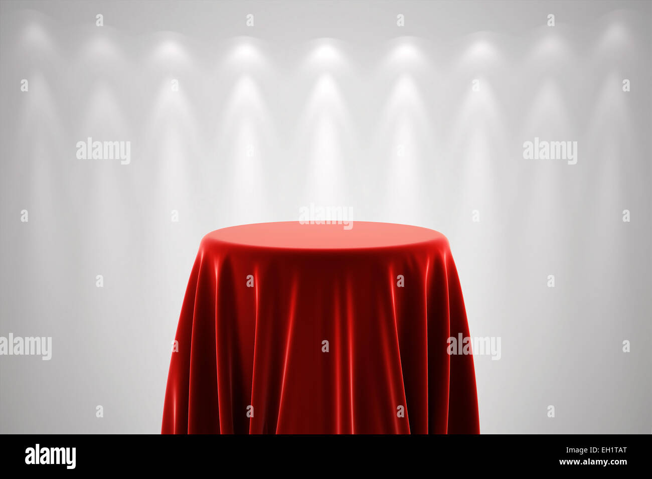 Round presentation pedestal covered with a red silk cloth in front of a white wall illuminated by spot lights - Stock Image