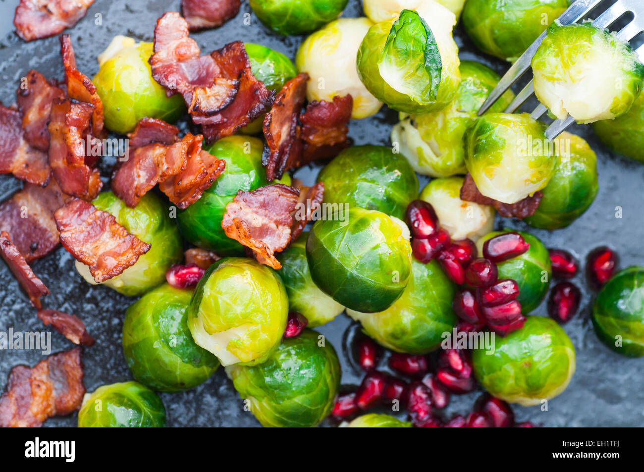 Buttered brussels sprouts with bacon and pomegranate. - Stock Image