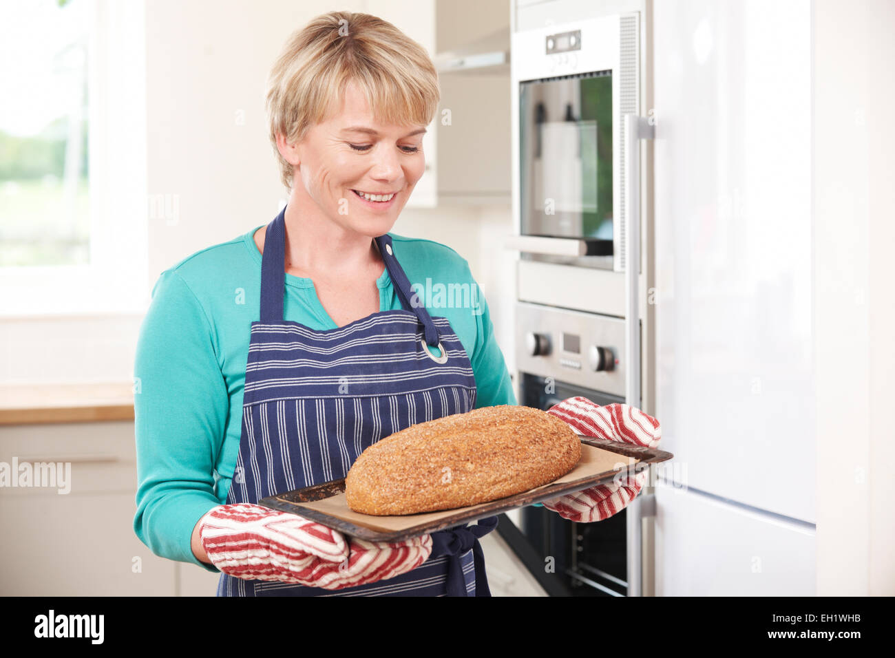 Woman Holding Tray With Home Made Loaf Of Bread Stock Photo