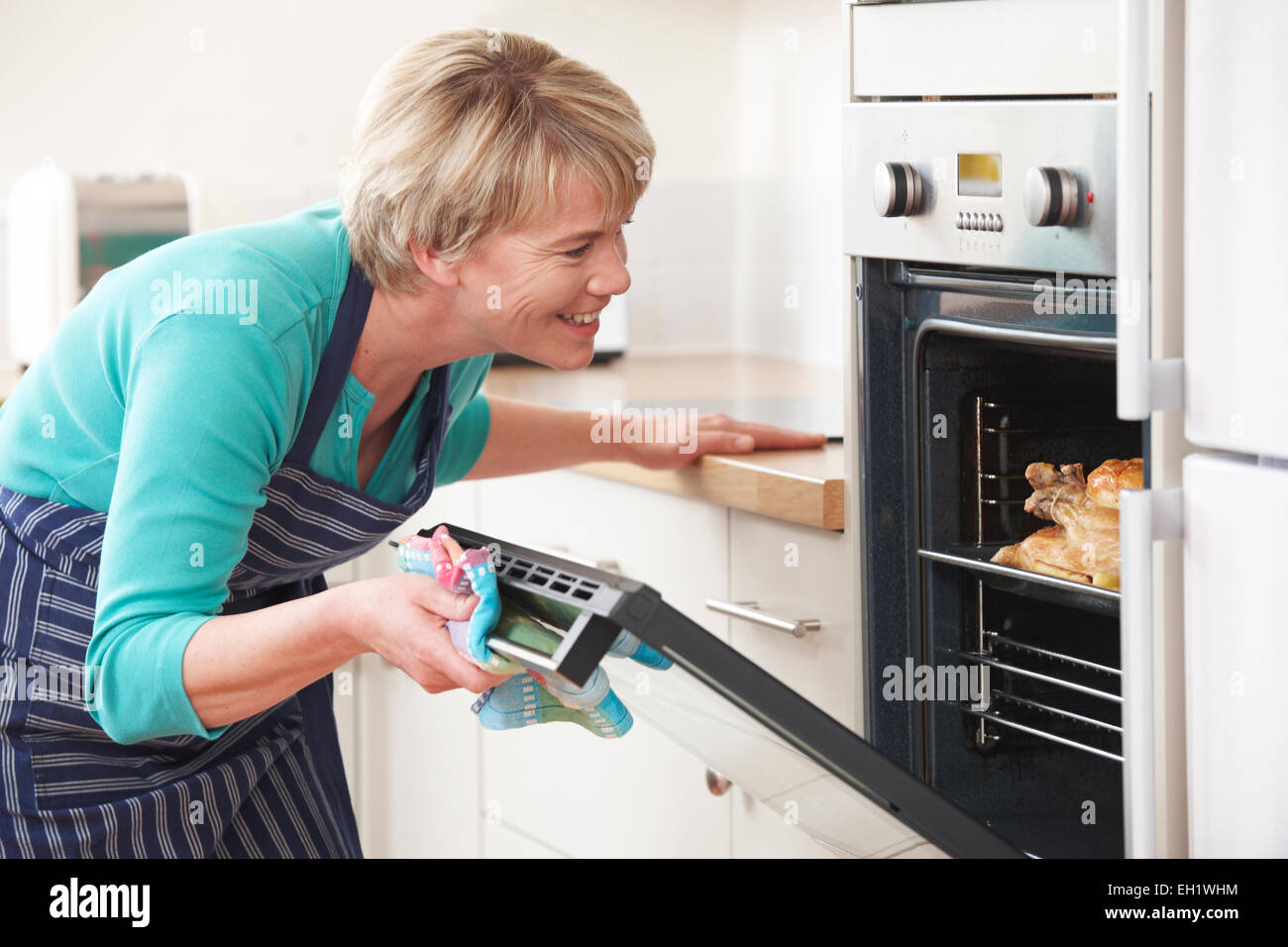 Woman Looking At Chicken Roasting In Oven - Stock Image