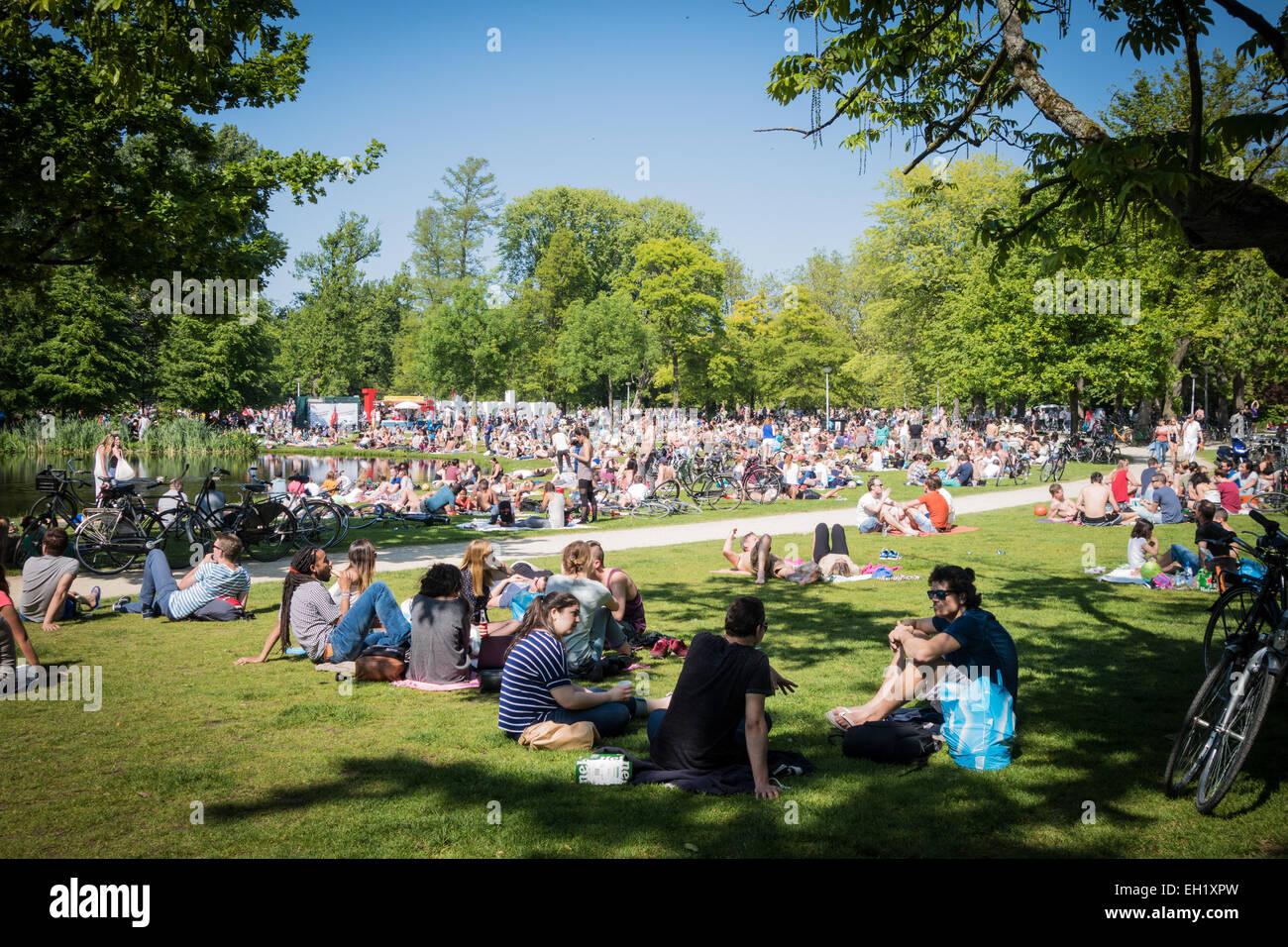 Crowds of people enjoying the sun in Vondelpark amsterdam - Stock Image