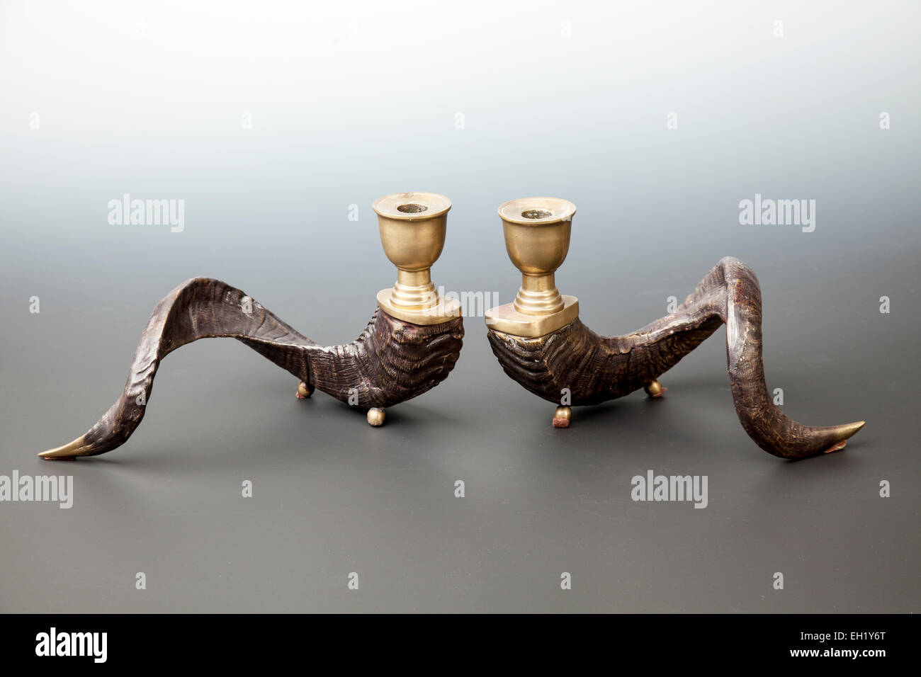 Pair of vintage brass ram horn candle holders. - Stock Image