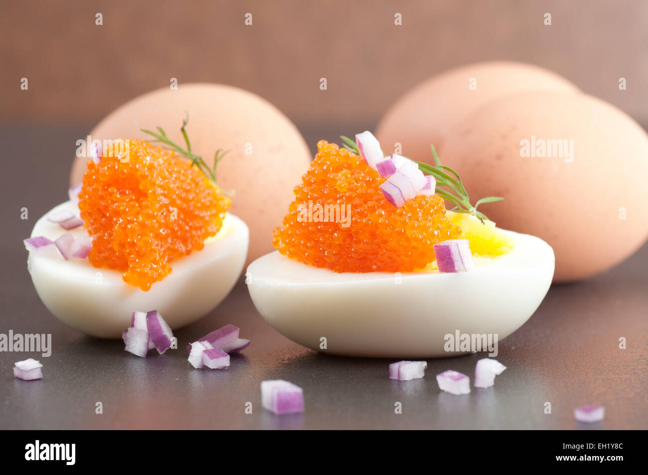 Egg halves with caviar, spanish onion and dill. - Stock Image