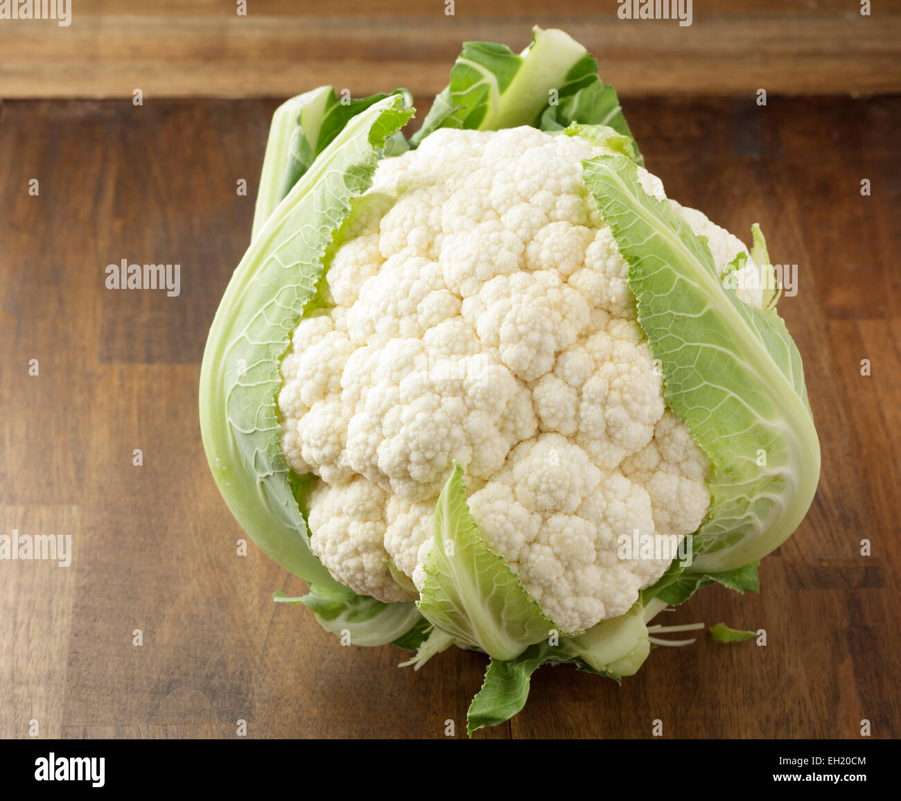 whole cauliflower on wooden table - Stock Image
