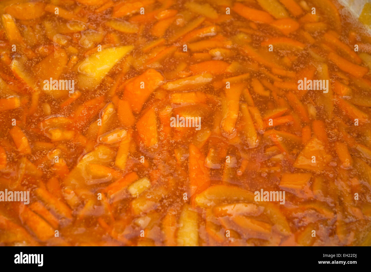 Making marmalade - coarsely chopped Seville oranges and lemon peel  gently simmering within a preserving pan. - Stock Image