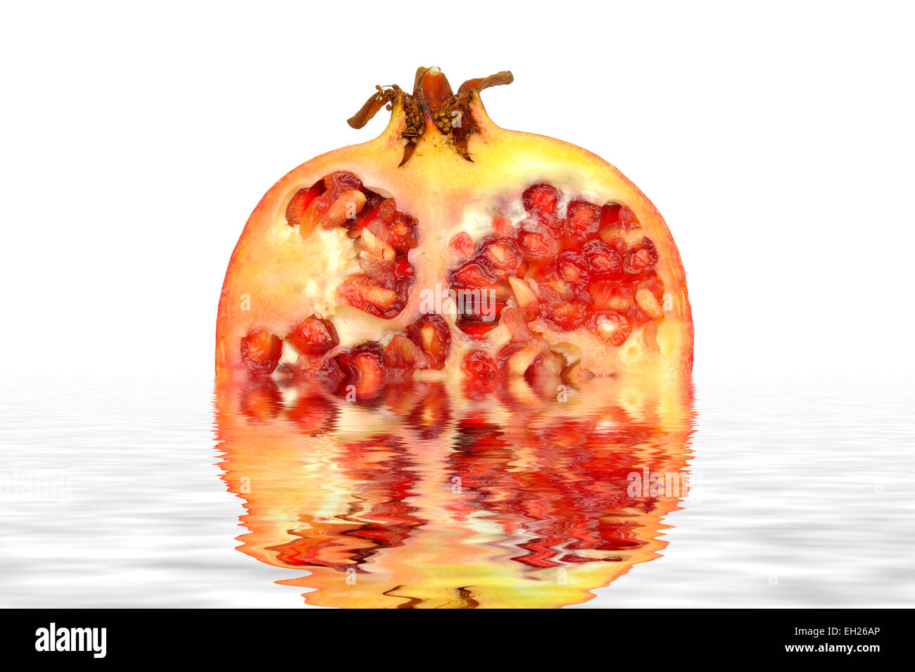A Pomegranate digitally reflected in a pool of water - Stock Image