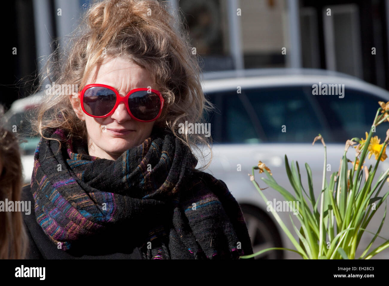 1aee8743668 Young woman looks at the camera through enormous red framed sunglasses -  Stock Image