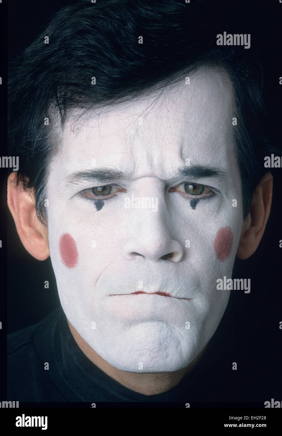 Mime, male, in white face, displaying anger, resentment - Stock Image