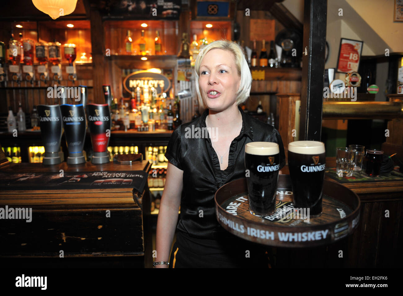 Bar Maid carries a tray of Guinness in a local pub, Lancashire. - Stock Image