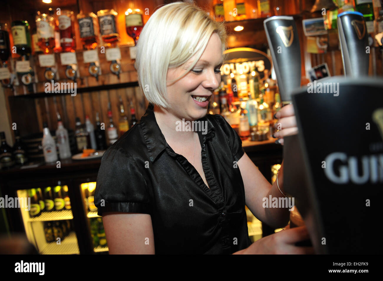 Barmaid pulls a pint in a local pub, Lancashire. - Stock Image