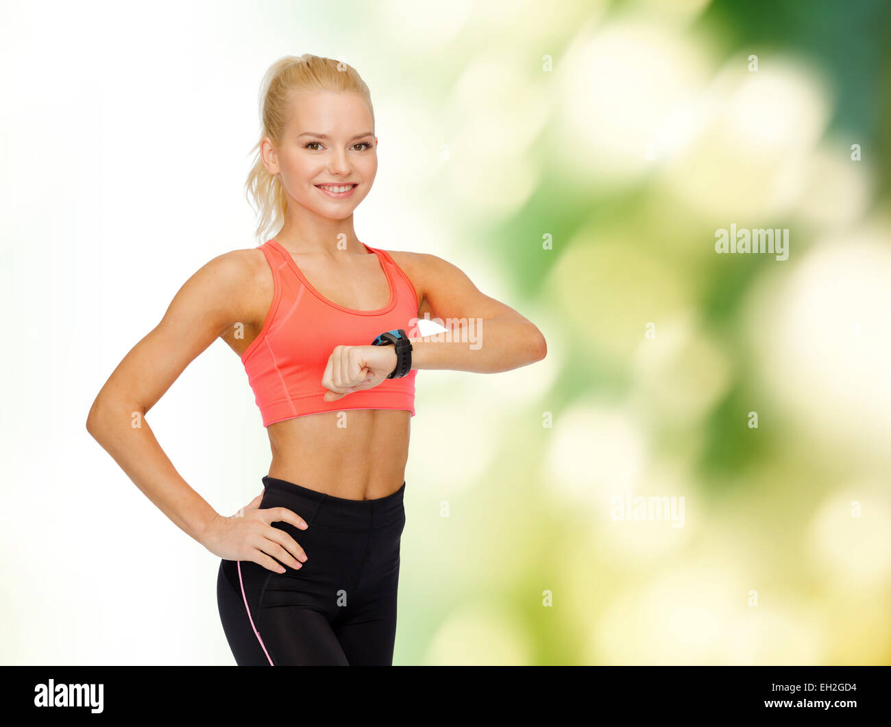 smiling woman with heart rate monitor on hand - Stock Image