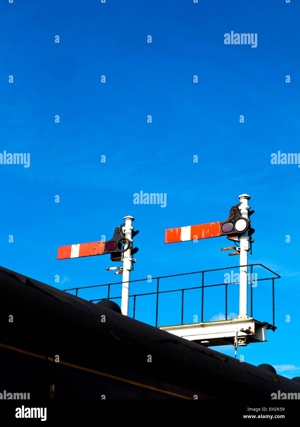 Railway semaphore stop signals against a blue sky on the Churnet Valley Railway, Staffordshire, England UK - Stock Image