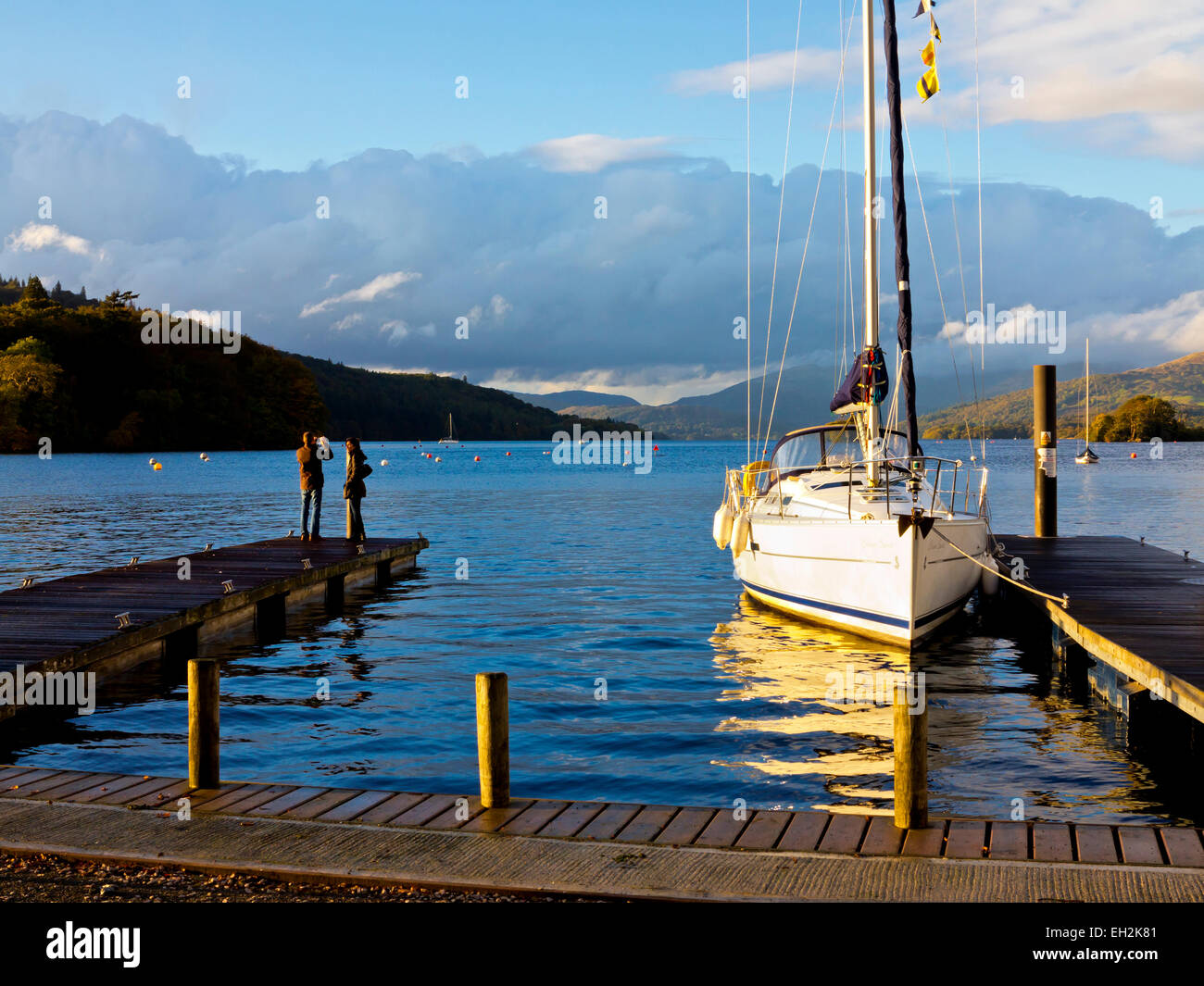 Sailing boat moored at a pier on Lake Windermere Lake District National Park Cumbria England UK with couple standing - Stock Image