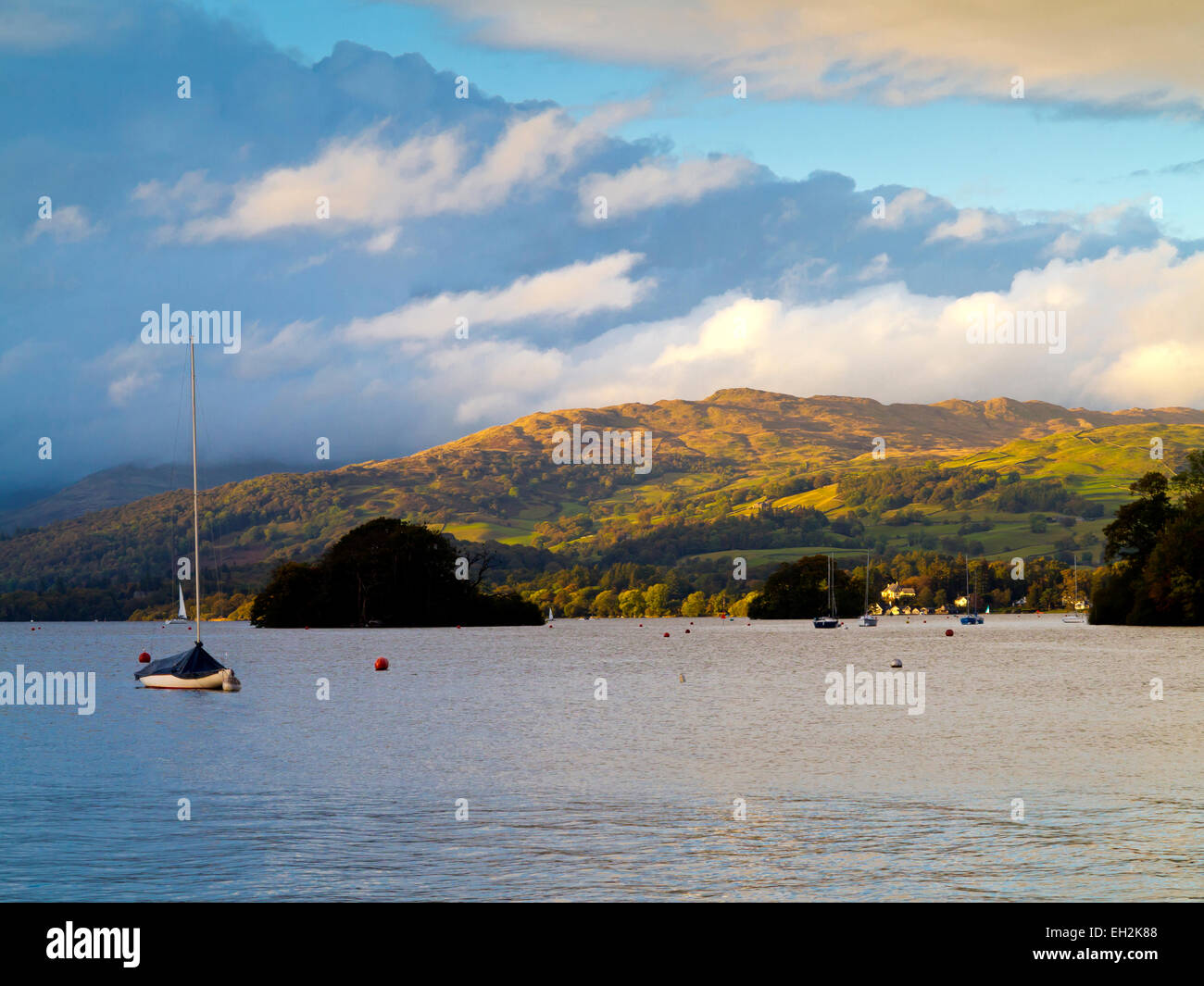 View across Lake Windermere in the Lake District National Park Cunbria UK showing boats on the water and fells in - Stock Image