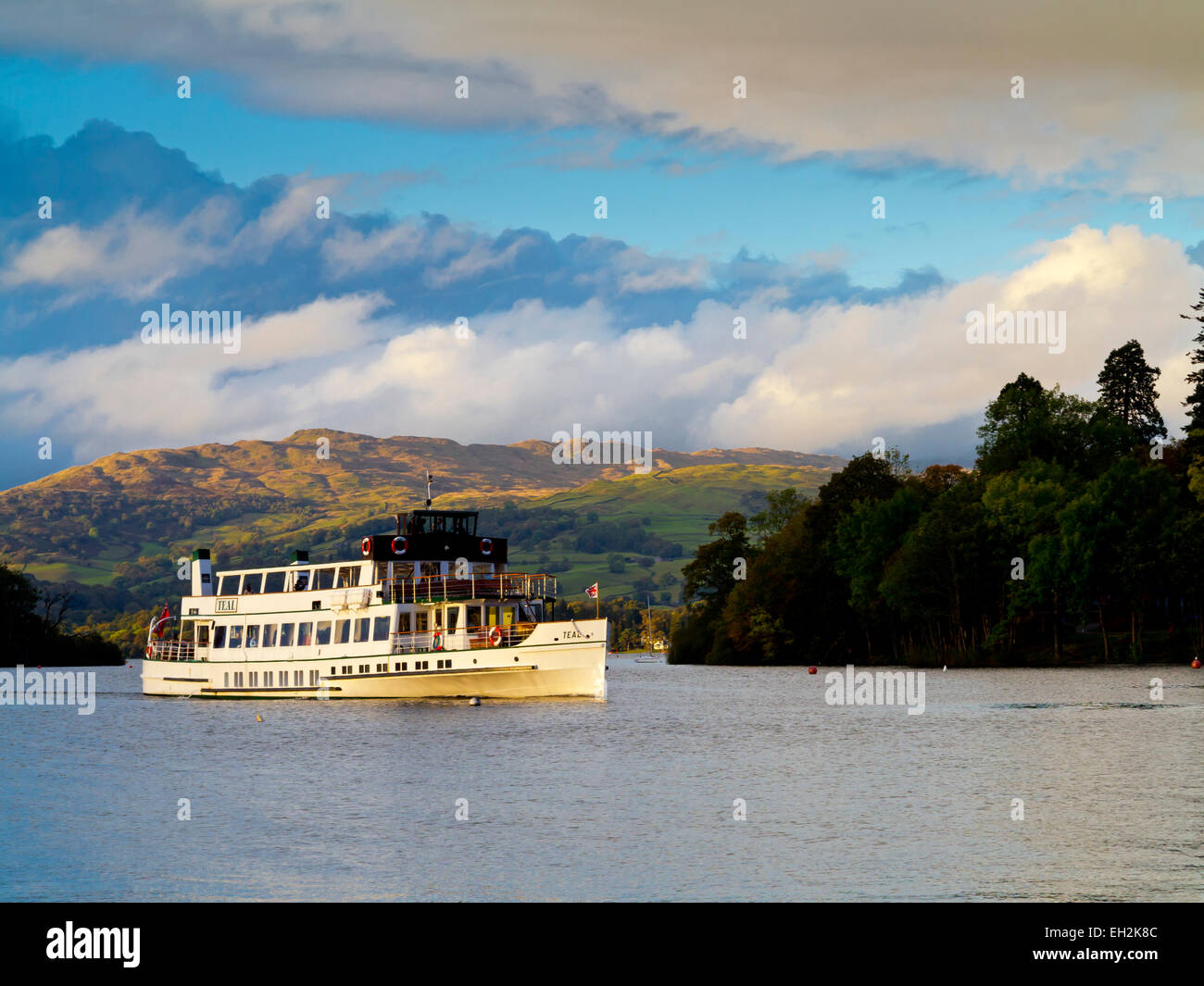 Passenger boat MV Teal sailing across Lake Windermere in the Lake District National Park with view of mountains - Stock Image