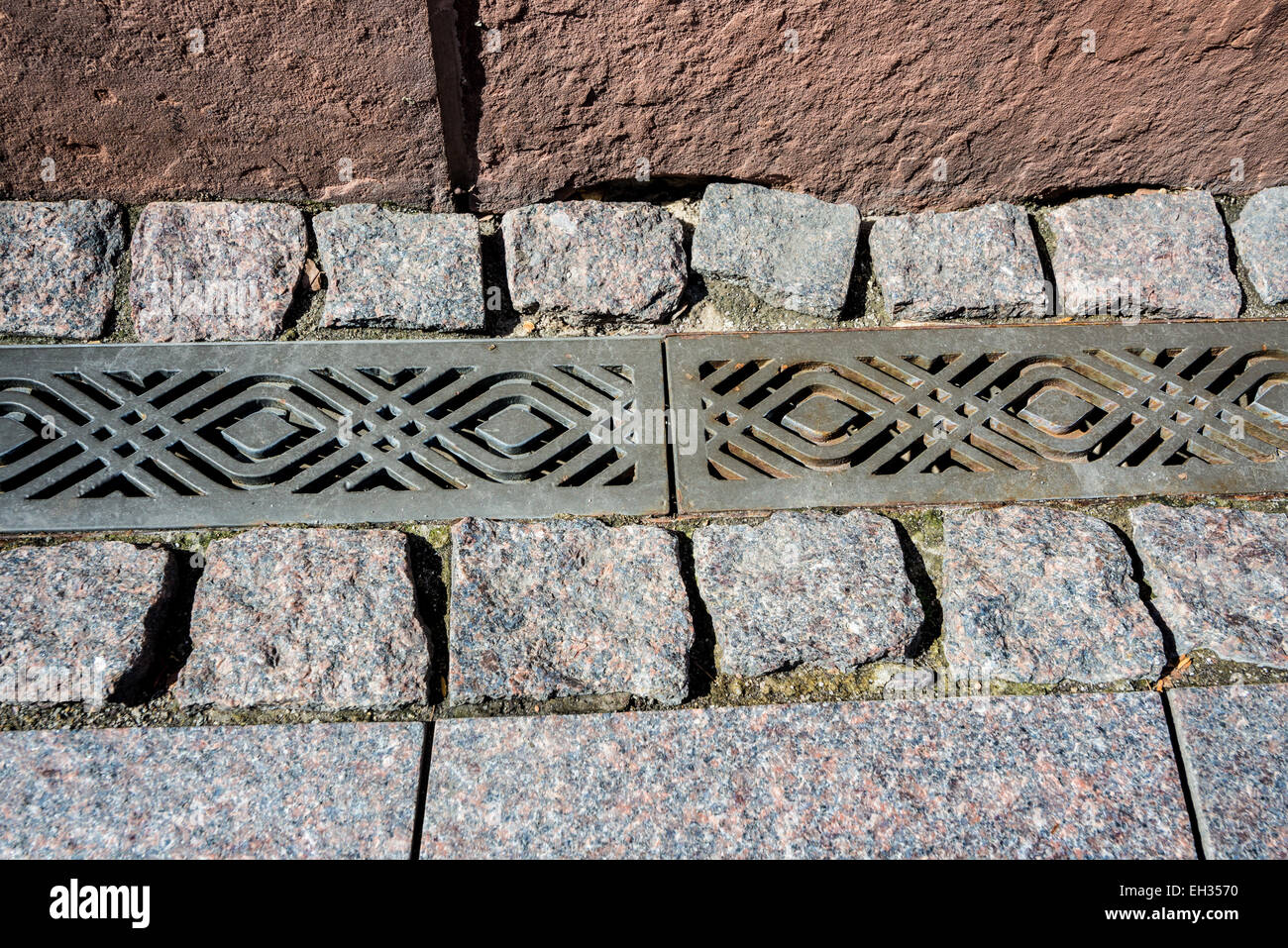 A decorative metal storm drain and permeable pavement in a public plaza - Stock Image