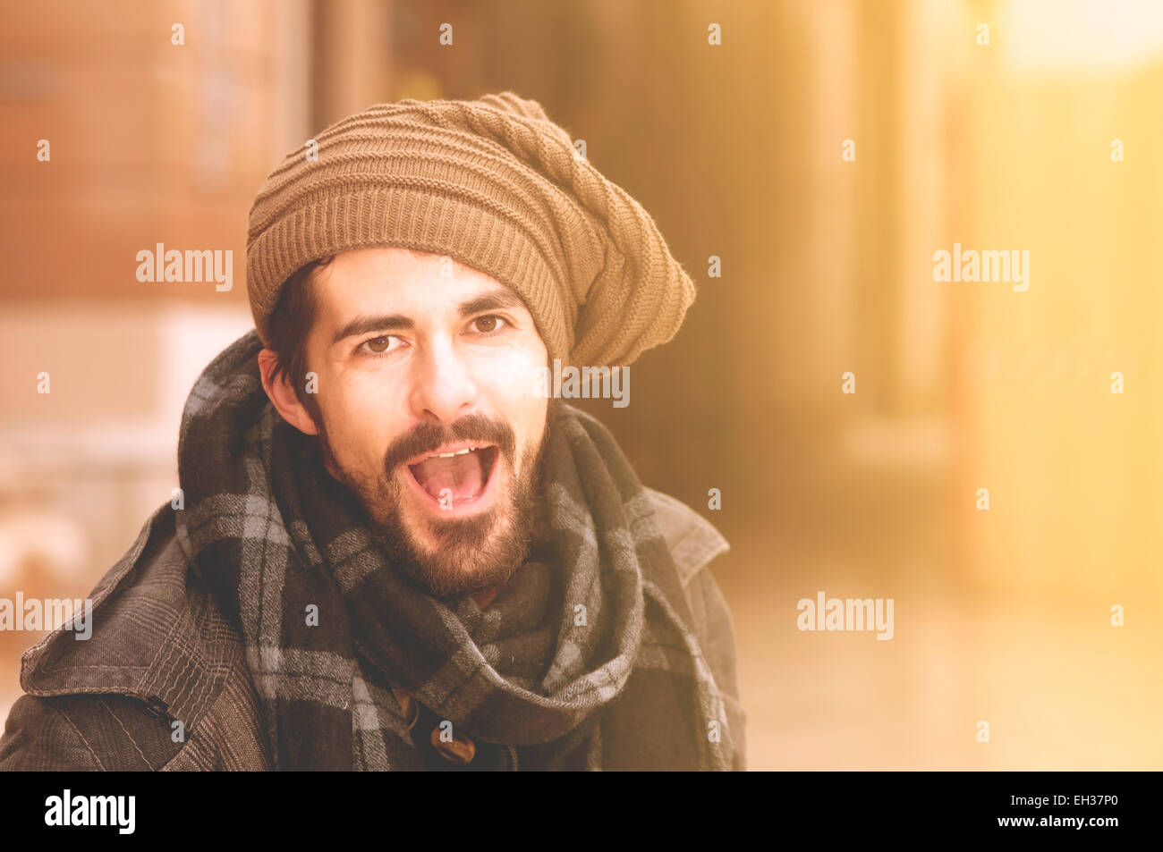 hipster man having fun shouting in the city instagram tones - Stock Image