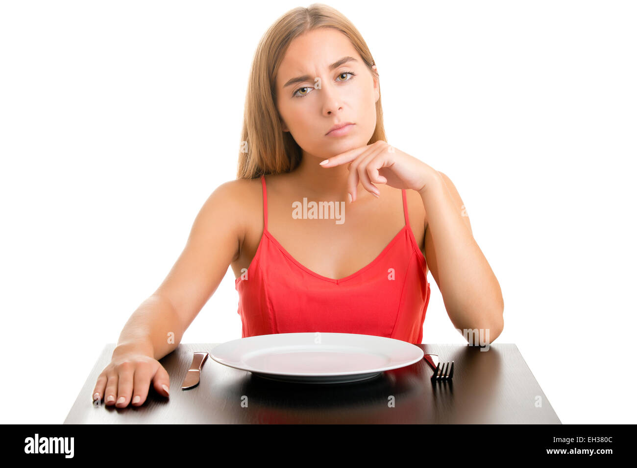 Hungry woman on a diet waiting with an empty place, isolated in white - Stock Image