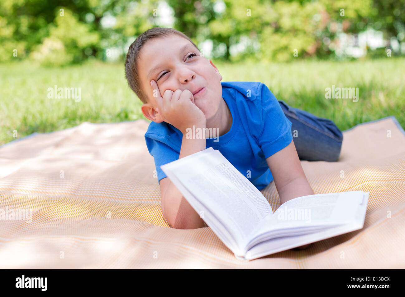 Boy thinking on the book with humour. Selective focus - Stock Image