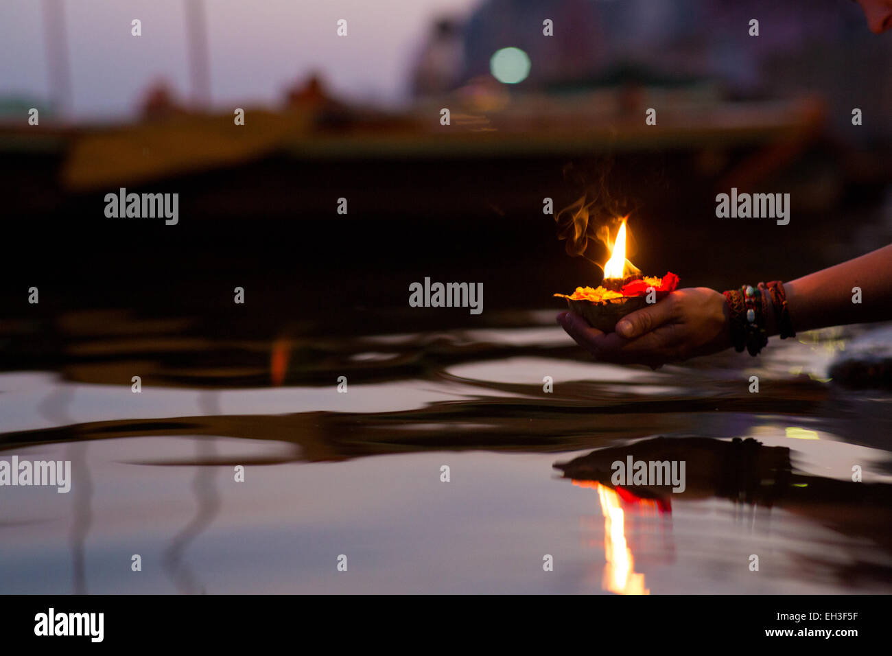 Closeup of a womans hand putting a fire blessing (puja) in the ganges river in Varanasi at sunset - Stock Image