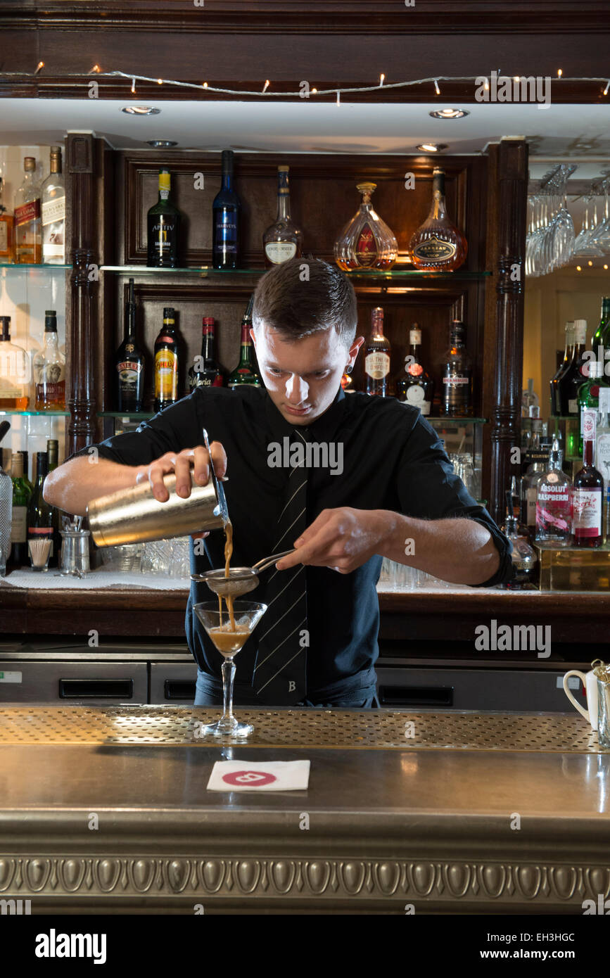 A male barman, bar tender, mixologist makes a fantastic cocktail in a high end restaurant / bar / public house - Stock Image