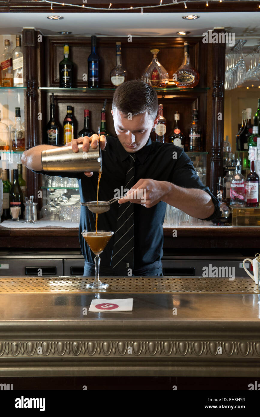 A male barman, bar tender, mixologist makes a fantastic cocktail in a high end restaurant / bar / public house Stock Photo