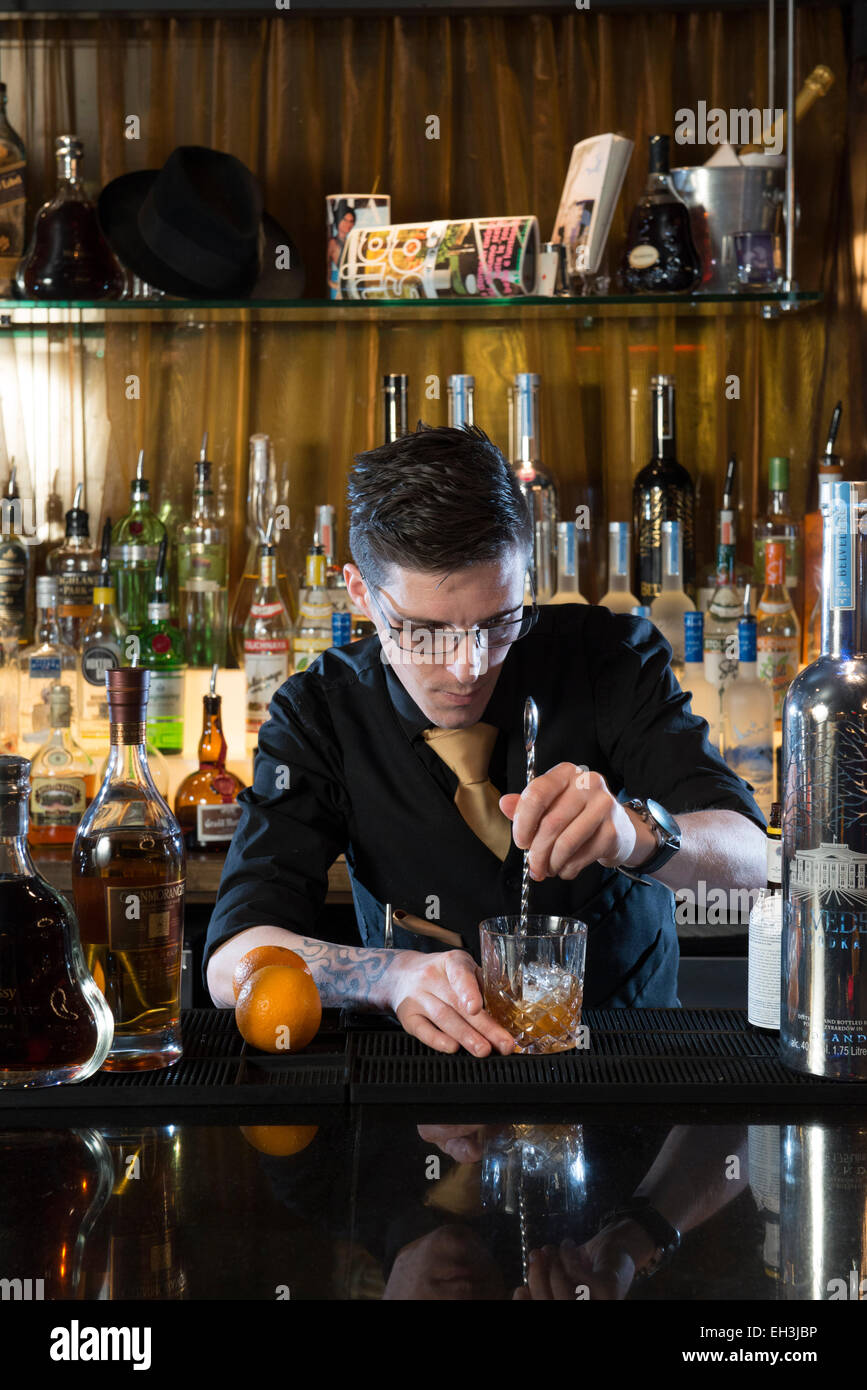 A femalebarman, bar tender, mixologist makes a fantastic cocktail in a high end restaurant / bar / public house - Stock Image