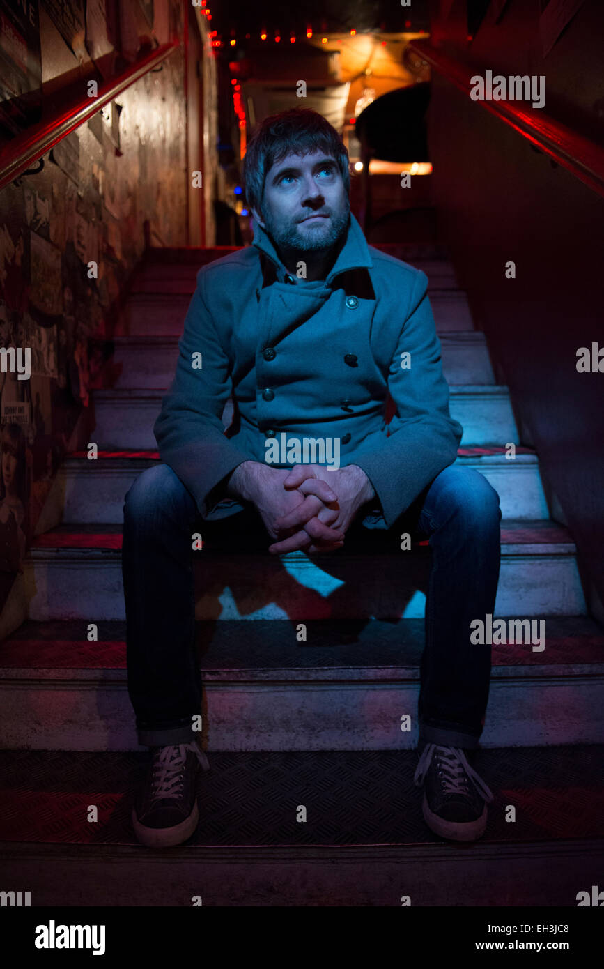a bar owner sits on some steps in his pub in Brighton lit by blue light Stock Photo