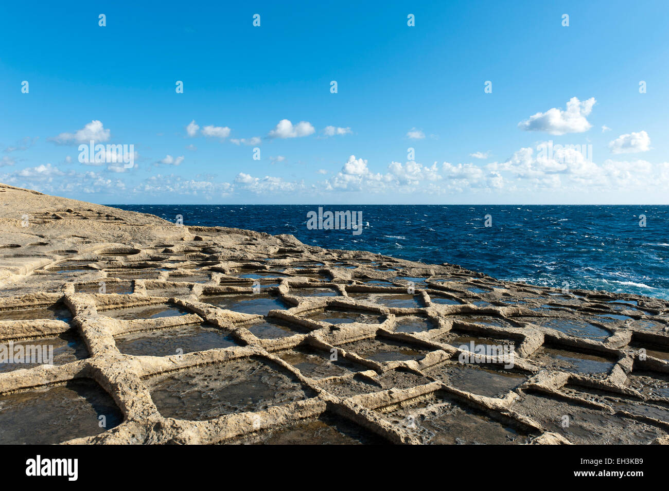 Sandstone formations on the coast, sea salt extraction in salt pans, Xlendi, Gozo, Malta - Stock Image