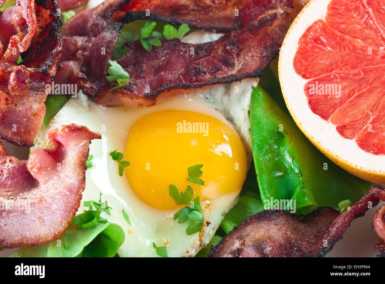 Fried egg with bacon, lettuce and grapefruit. - Stock Image