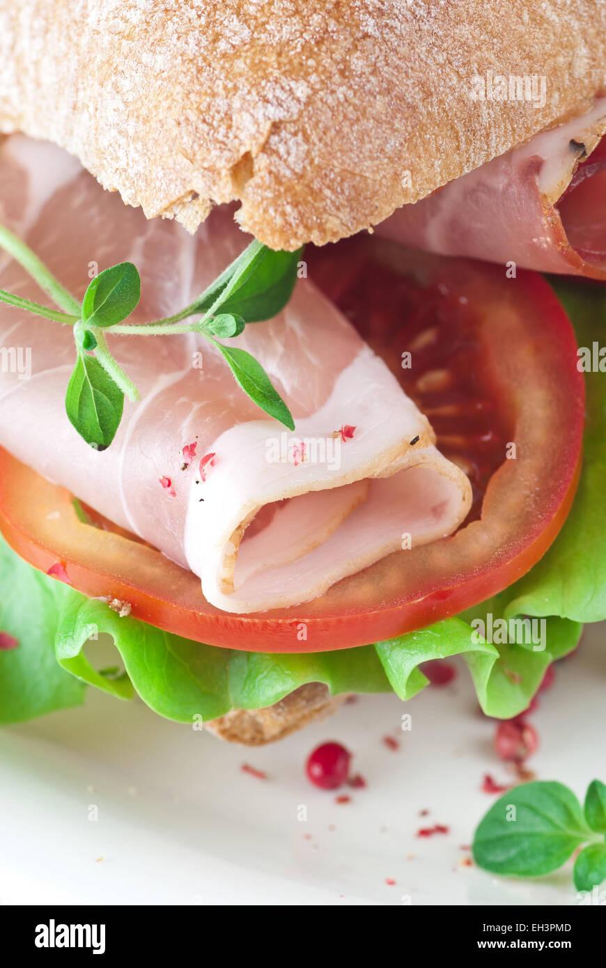 Ciabatta sandwich with ham, tomato and lettuce. - Stock Image