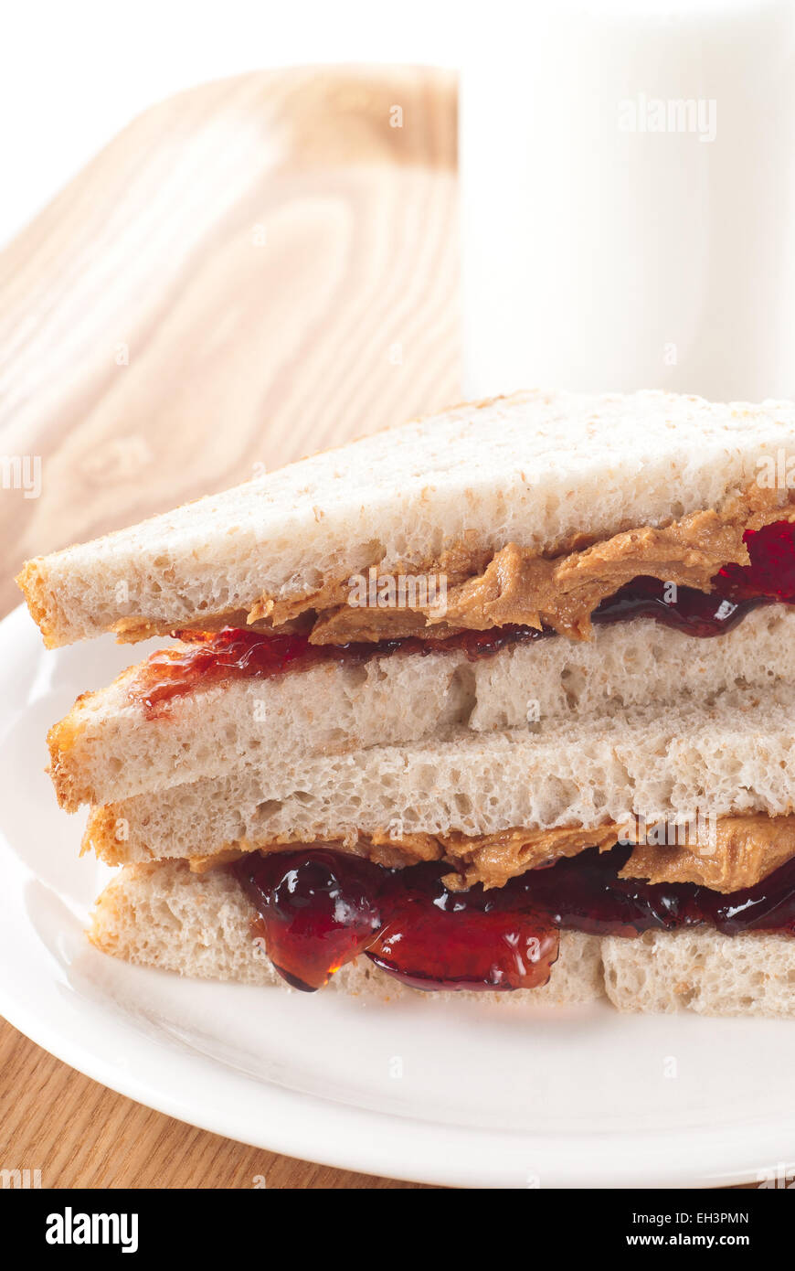 Peanut butter and jelly sandwich with a glass of milk. - Stock Image