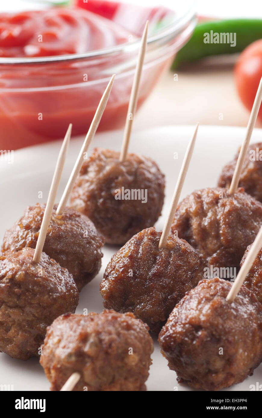 Meatballs on toothpicks, served with tomato sauce. - Stock Image