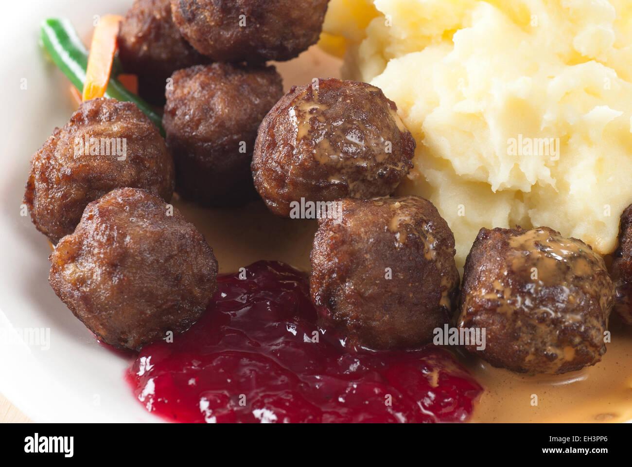 Meat balls with mashed potato, brown cream sauce and lingonberry preserves. - Stock Image