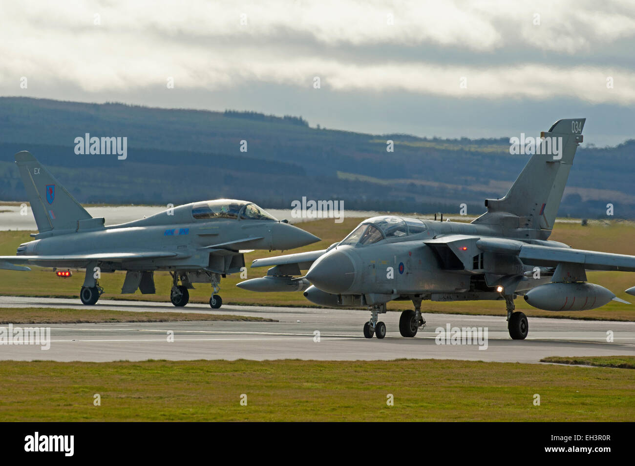 The old and new as an RAF GR4 Tornado taxis past the latest FRG4 Eurofighter Typhoon jet fighter.  SCO 9626. - Stock Image