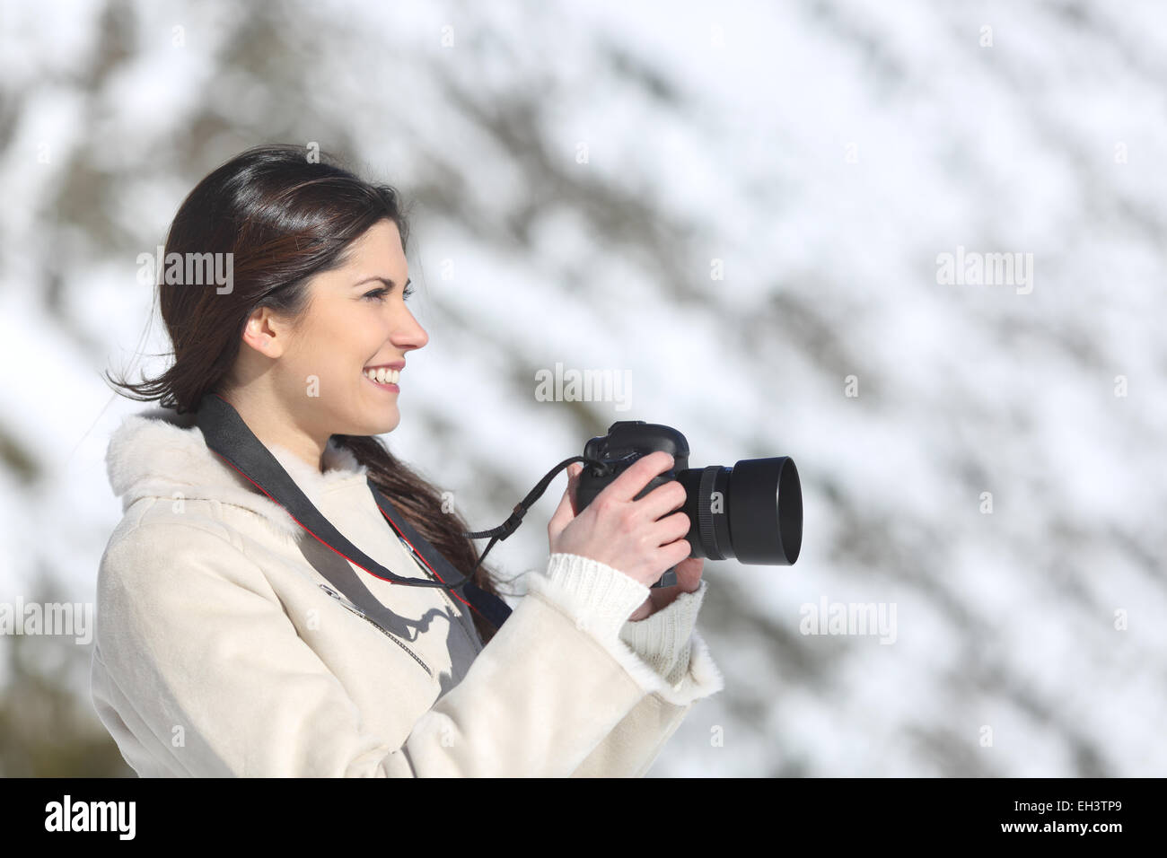 Tourist woman photographing on winter holidays with a snowy mountain in the background - Stock Image