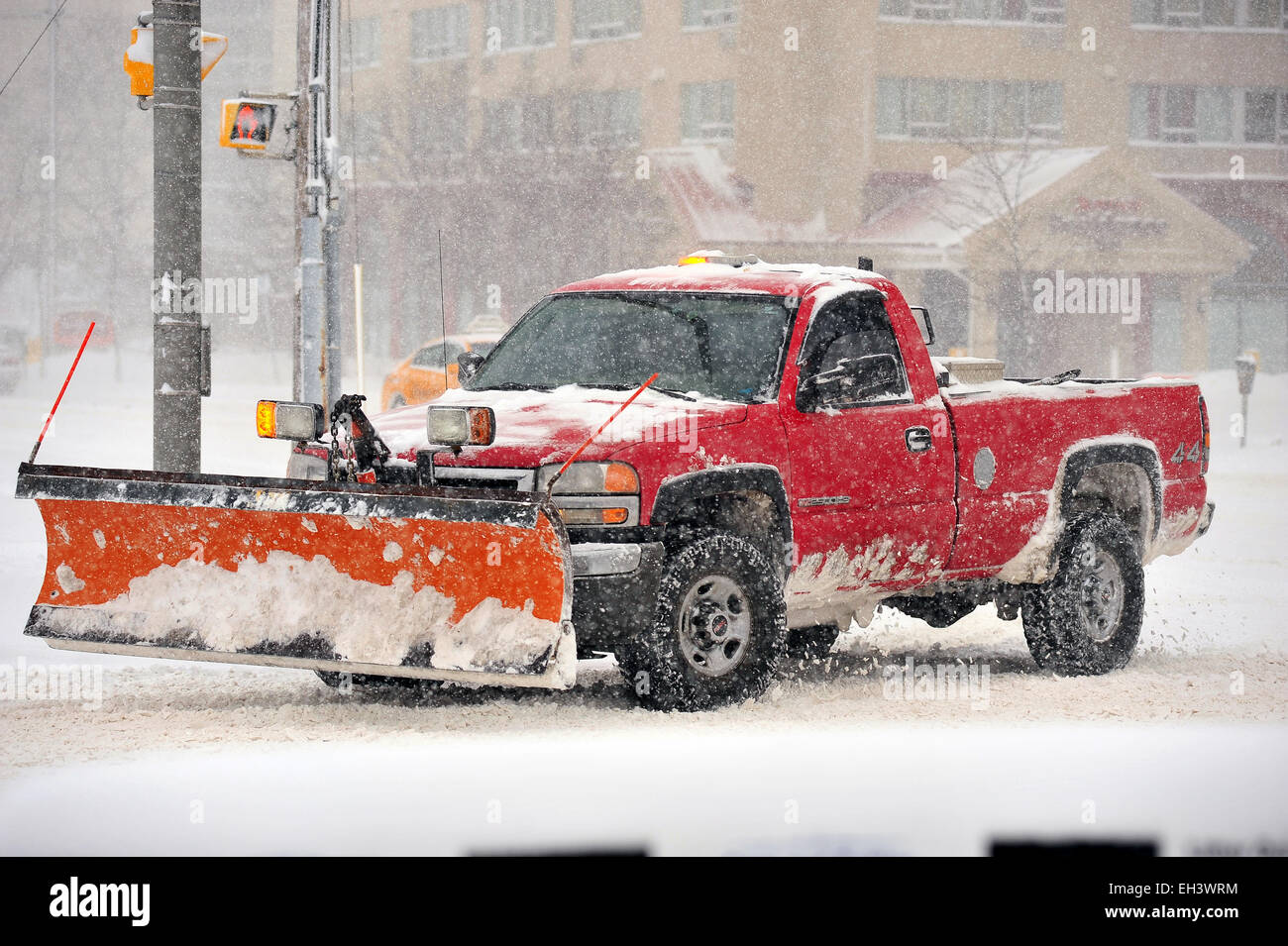 A snowplow attached to a red pick up truck in Canada. - Stock Image
